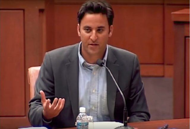 A man in a suit and no tie sits in front of microphone giving arguing a case before a Judge.