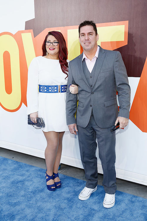 Amber and her husband stand on a blue carpet.