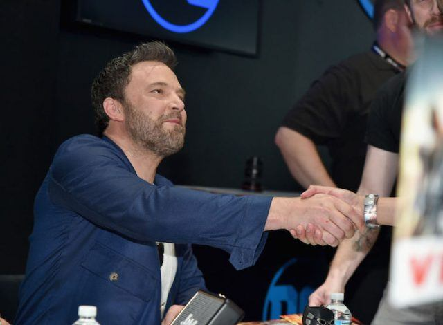 Ben Affleck in a blue jacket shaking someone's hand at Comic-Con.