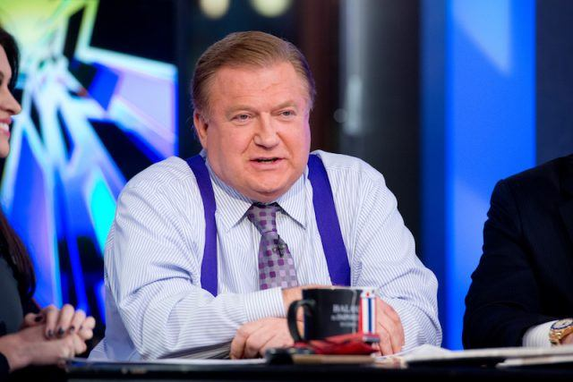 Bob Beckel sits in front of a desk with his co-stars.
