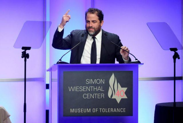 Brett Ratner speaks at a podium in front of a microphone.