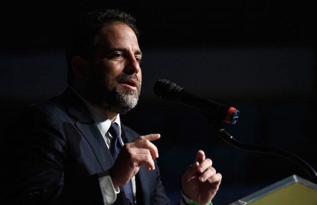 Brett Ratner speaks into a microphone while gesturing with his hands.