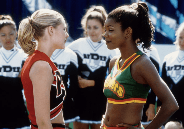 Two rival cheerleaders facing off in front of a crowd of performers.