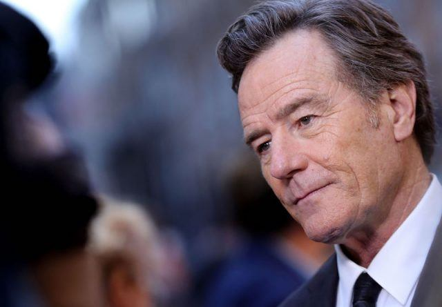Bryan Cranston posing for photos while in a black suit.