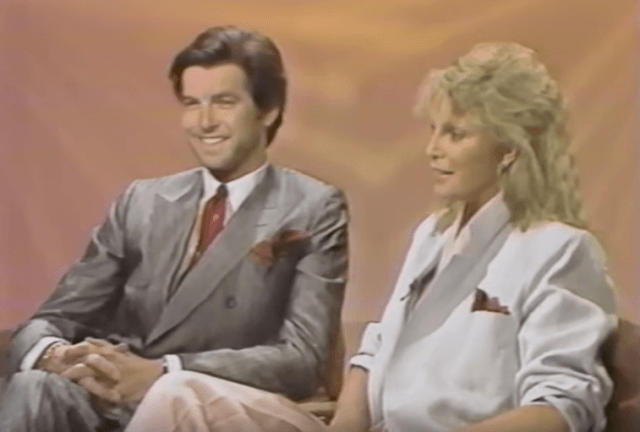 Pierce Brosnan and Cassandra Harris sitting together while being interviewed.