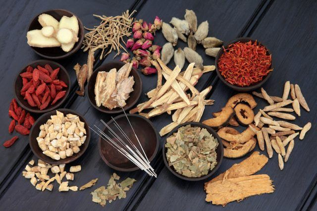 Chinese herbal medicines on a black wooden table.