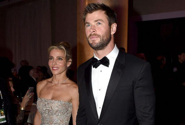 Elsa Pataky and Chris Hemsworth hold hands while walking into a theatre together.