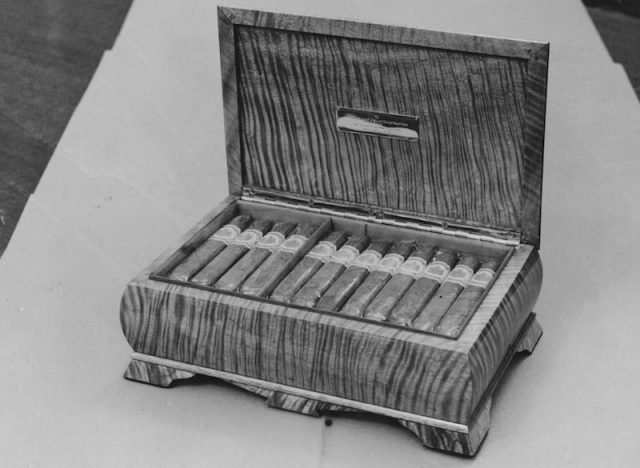 A box of cigars laid out on in a brown box.