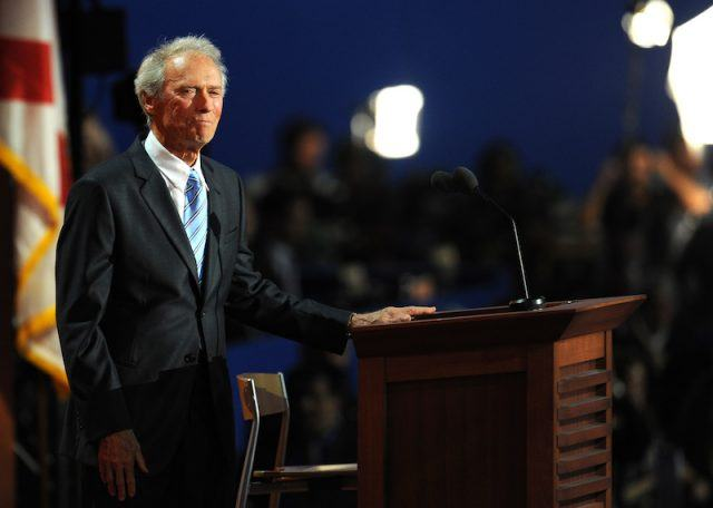 Clint Eastwood posing in front of a podium.
