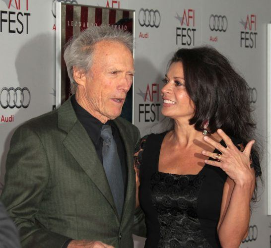 Clint and Dina Eastwood pose for photos on a red carpet.