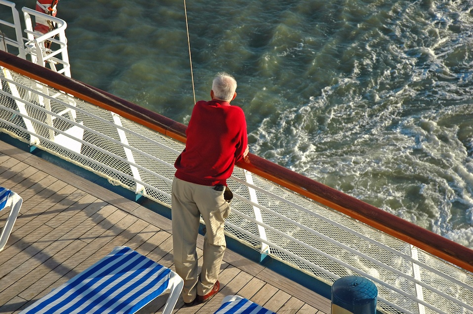 A senior stands on the rear deck of a cruise ship