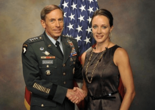 Paula Broadwell and David Petraeus posing for a photograph in front of a flag.