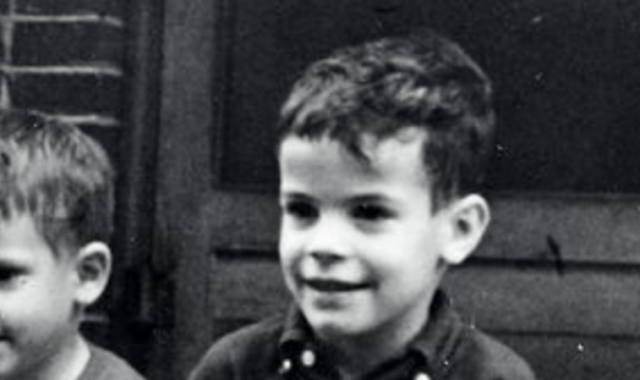 Dennis Martin smiling while sitting next to a young boy.