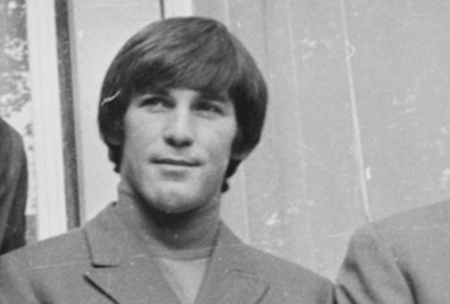 Dennis Wilson smiling while standing with his band mates.