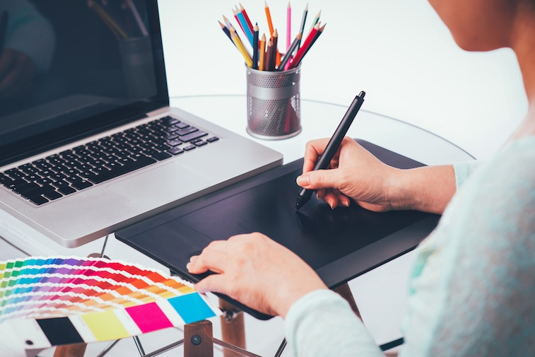 Designer using graphics tablet and colour charts