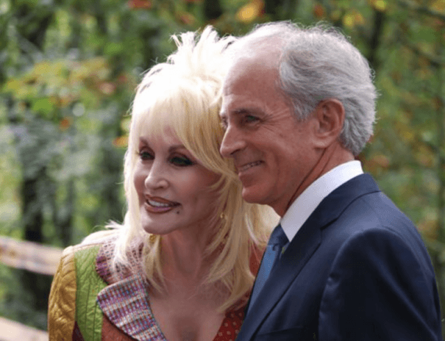Dolly Parton and Carl Dean smile as they pose closely together.