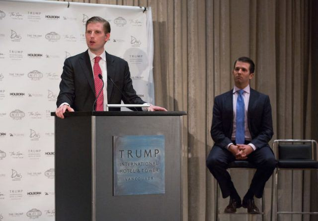 Eric Trump and Donald Trump Jr address an audience on stage.