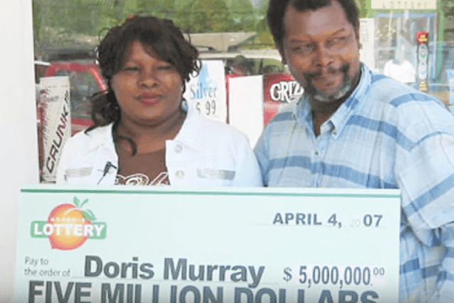 Doris Murray standing with her partner while holding a lottery ticket.