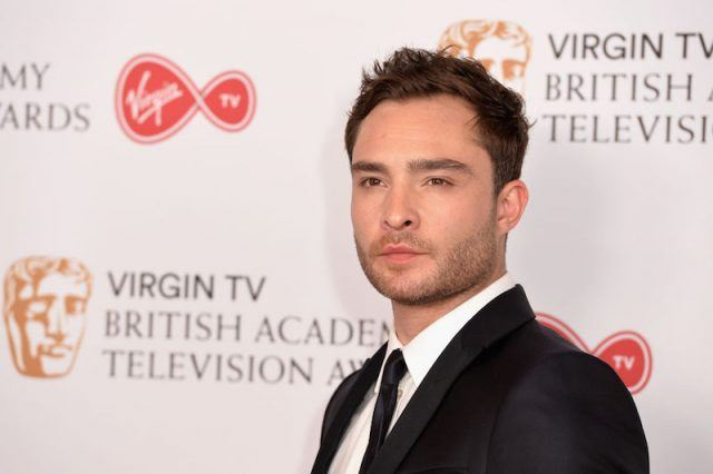 Ed Westwick posing in a black suit.