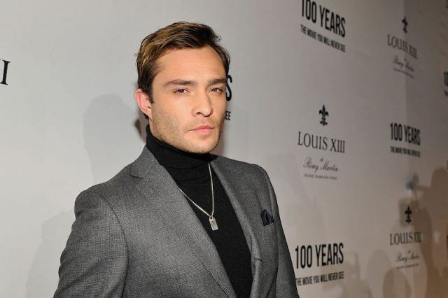 Ed Westwick posing on a red carpet in a black turtle neck sweater and gray blazer.