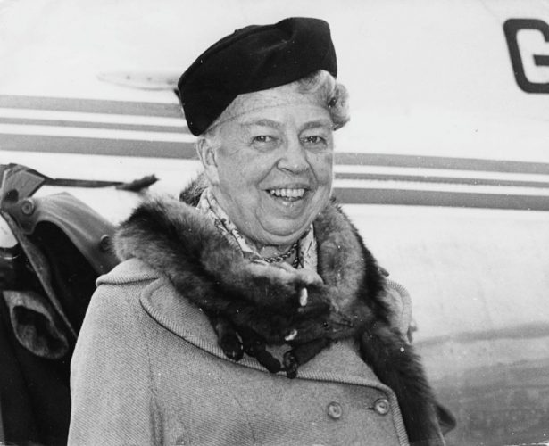 Eleanor Roosevelt, wife of President Franklin D Roosevelt smiles while standing in front of a plane.