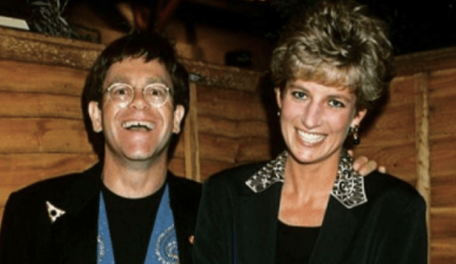 Elton John and Princess Diana smile as they pose for a photograph.