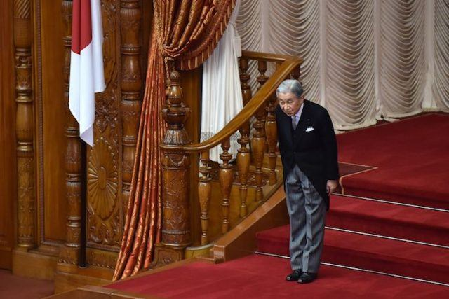 Japan's Emperor Akihito bows while standing on red stairs.