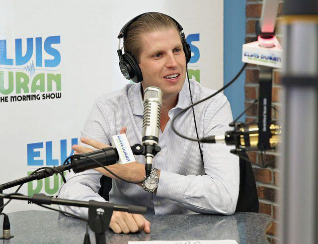 Eric Trump wearing headsets as he sits in front of a microphone.