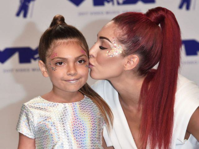 Farrah kisses her daughter while they both have decorative face paint on.