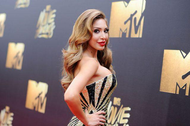 Farrah Abraham poses in a black and gold gown on the MTV Movie Awards red carpet.