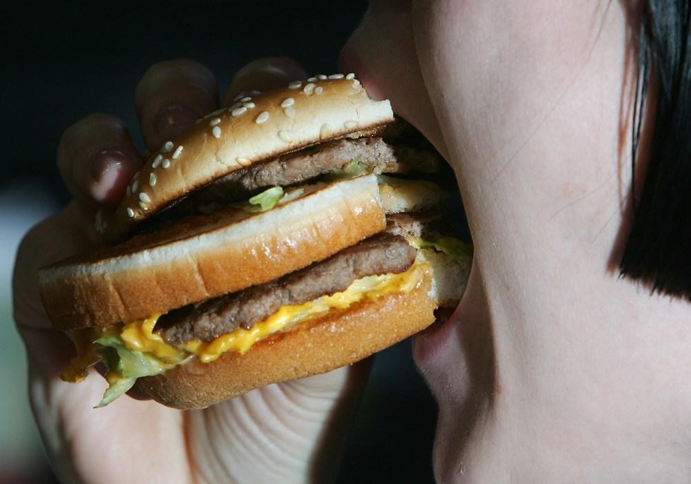 Lady eats a beefburger