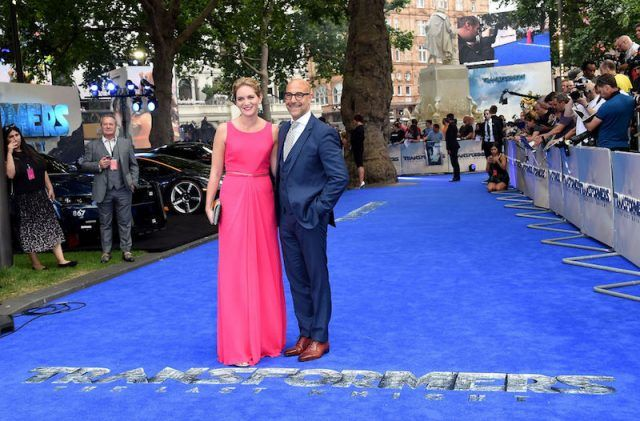 Felicity Blunt and Stanley Tucci posing together on a blue carpet.
