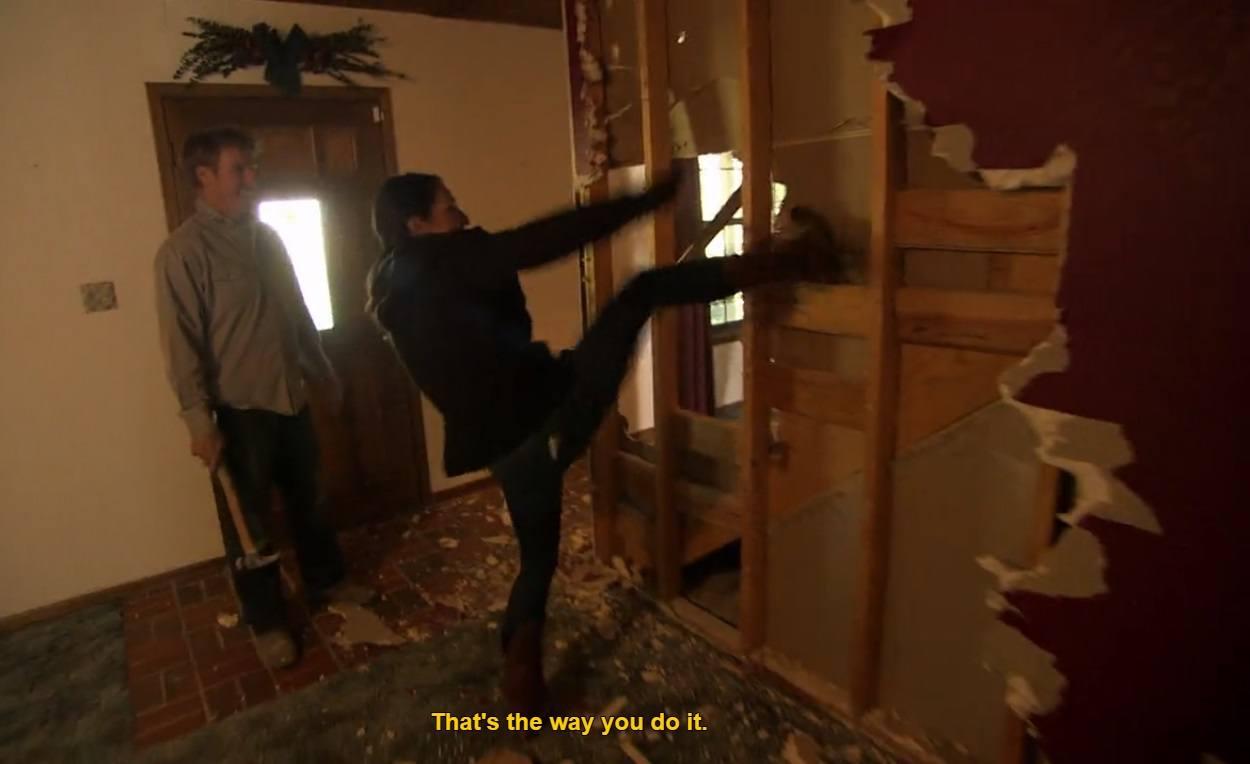Joanna kicks down wall