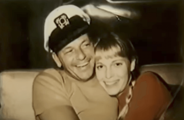 Frank Sinatra and Mira Farrow embracing on a couch as they smile.