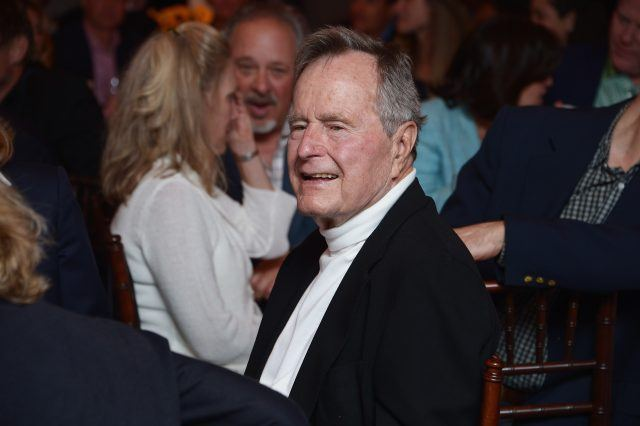 Former President Bush sits at a table with other guests.