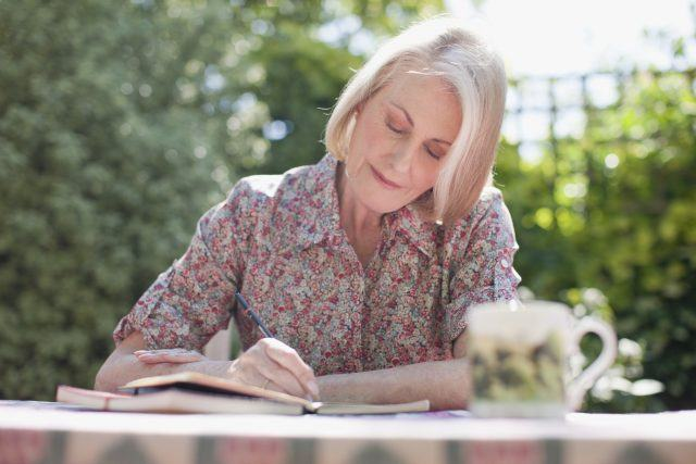 Woman writing in journal at patio table