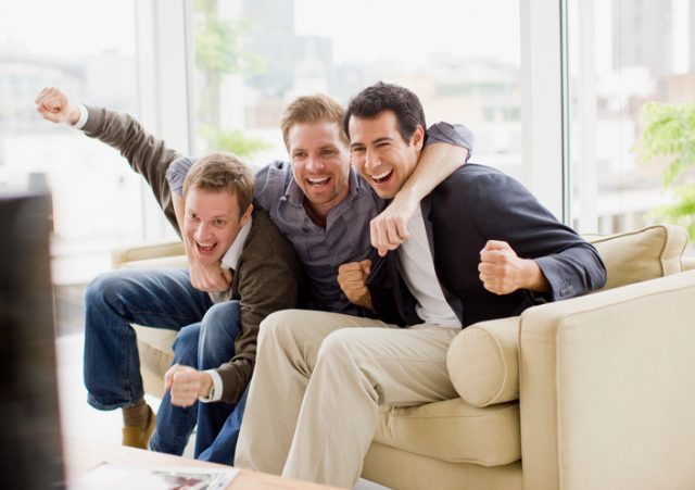 Cheering friends watching television