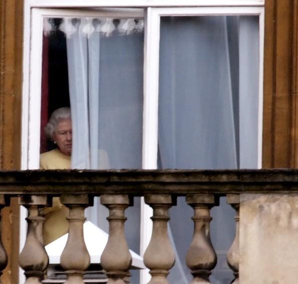 queen elizabeth peeks through a curtain at buckingham palace