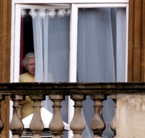 queen elizabeth peeks through a curtain at buckingham palace