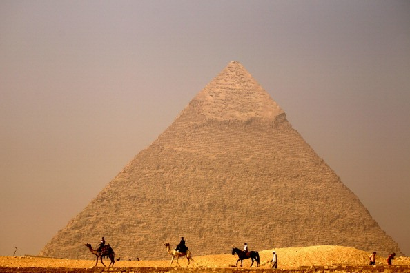 camels ride past the great pyramid