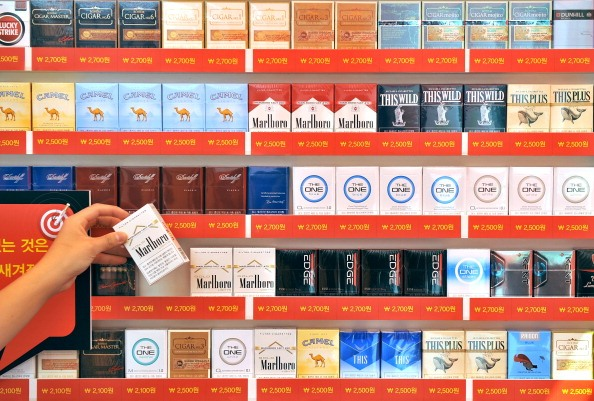 A campaigner holds a pack of cigarettes in front of a stand of tobacco boxes