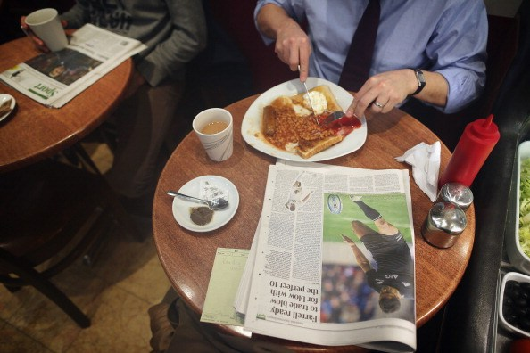 a table with toast and jam, coffee, and a newspaper in a cafe