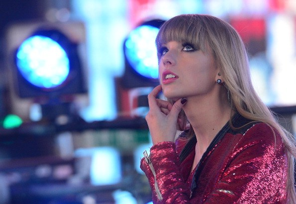 taylor swift in red with her hand on her chin