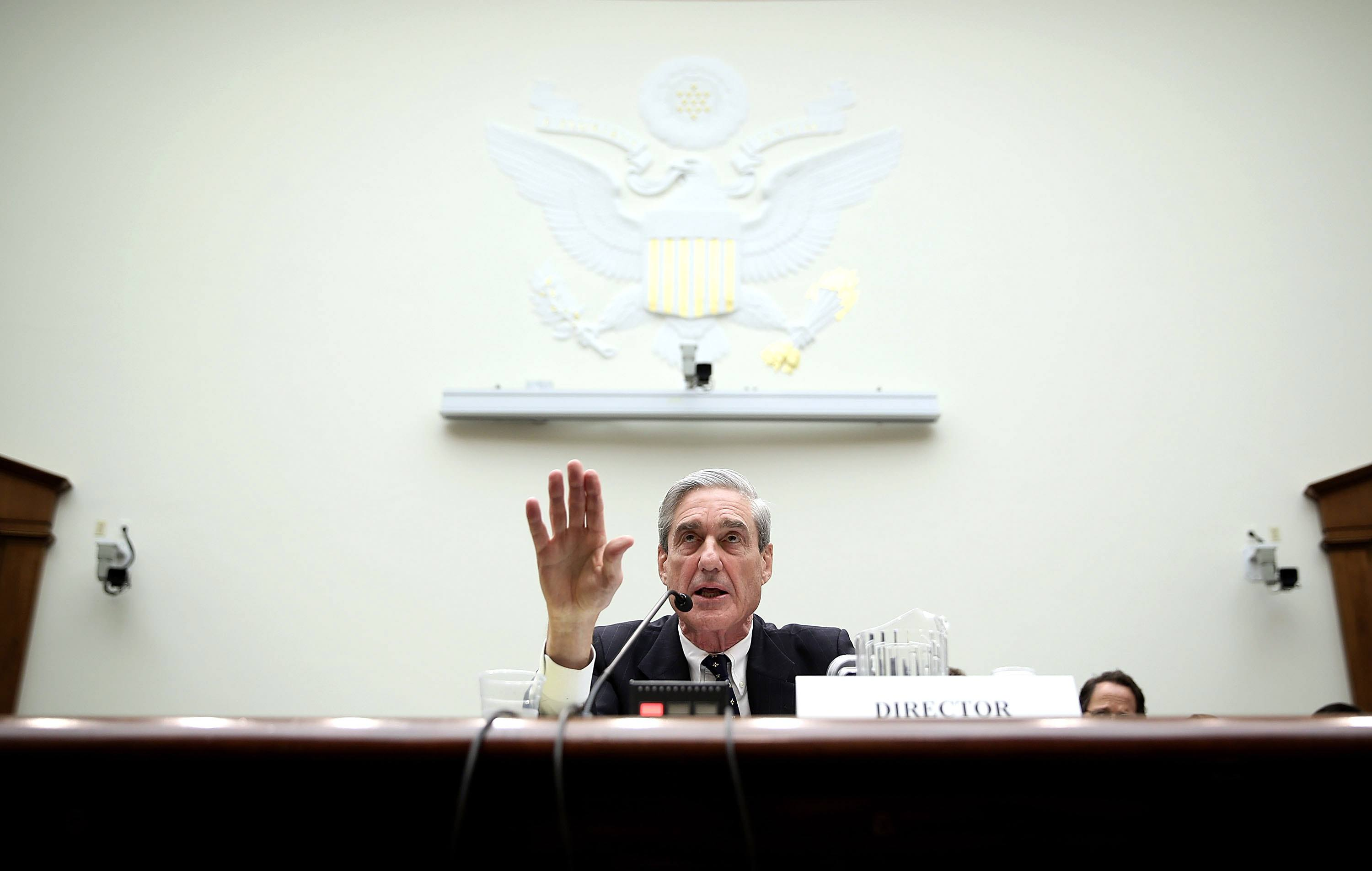 Mueller sitting at a desk in front of large white wall.