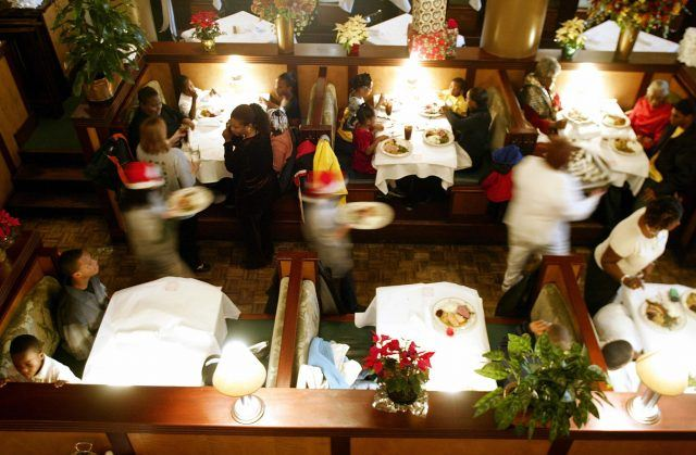 children and their families sit down for a Christmas dinner at the District Chophouse & Brewery restaurant