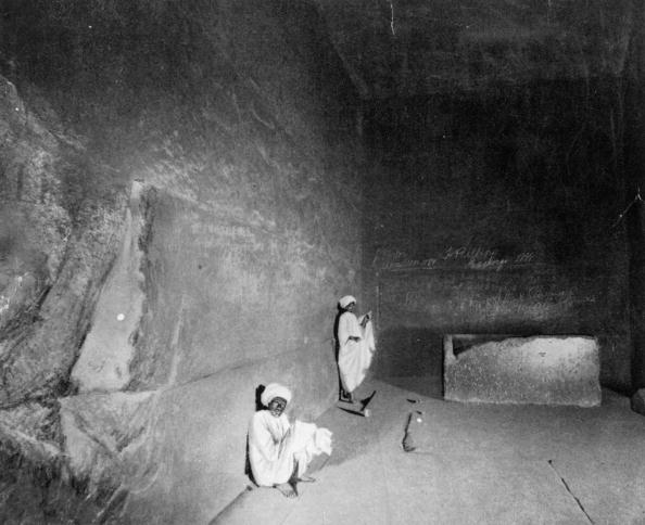 a black and white photo of archaeologists inside the great pyramid