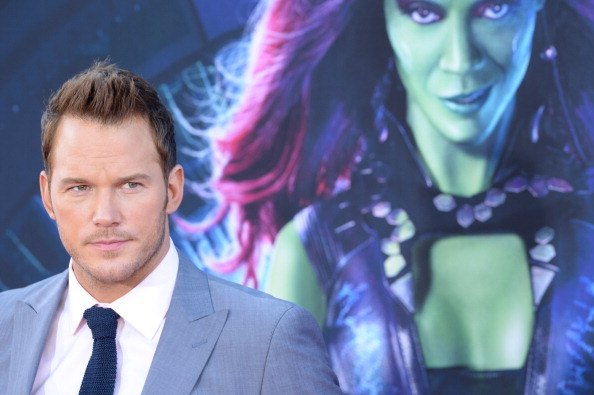 chris pratt in front of a guardians of the galaxy poster