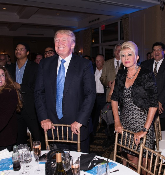 ivana and donald trump at a golf benefit standing behind gold chairs