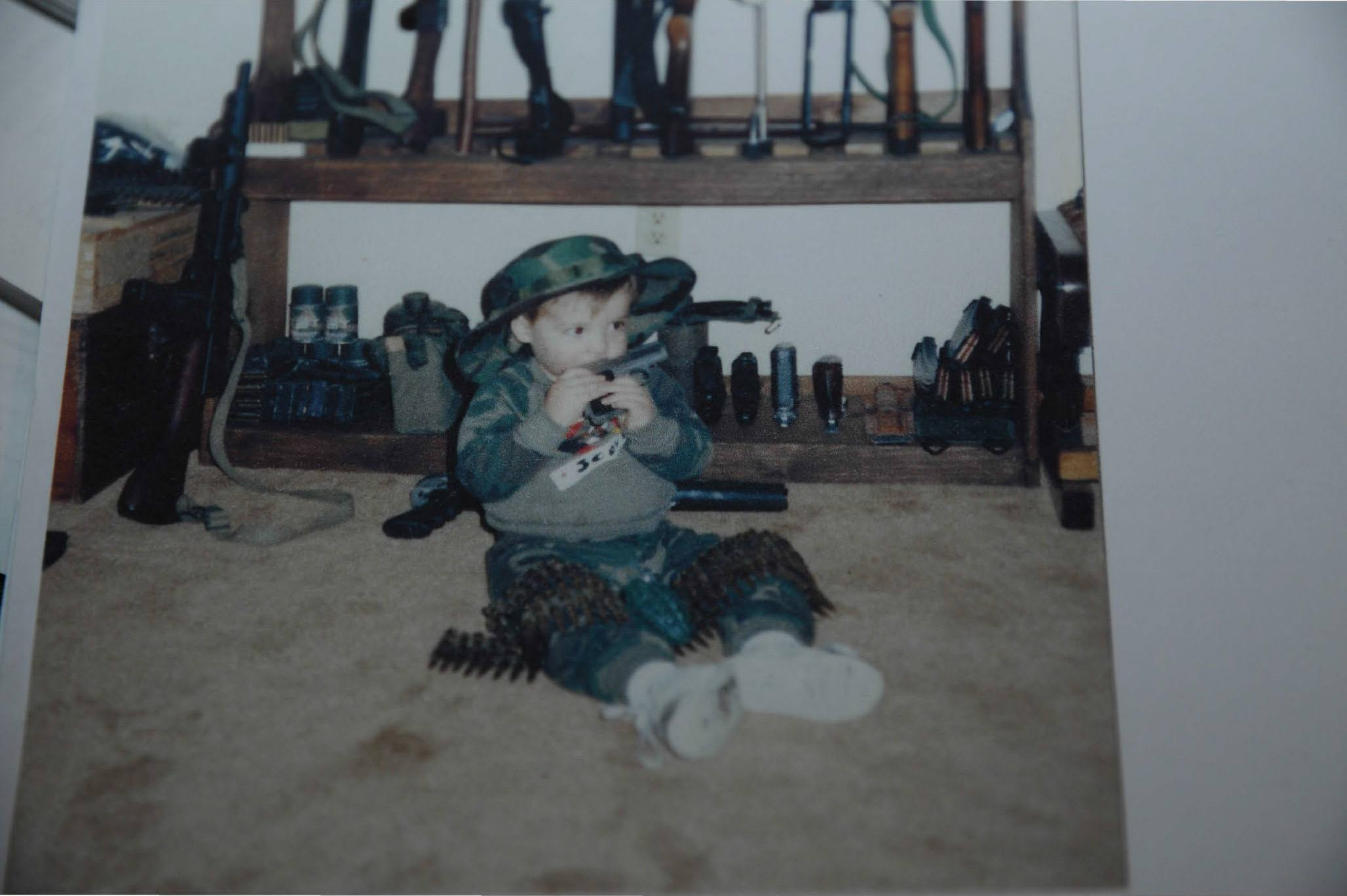 a child adam lanza wearing an ammunition belt by a rack of guns