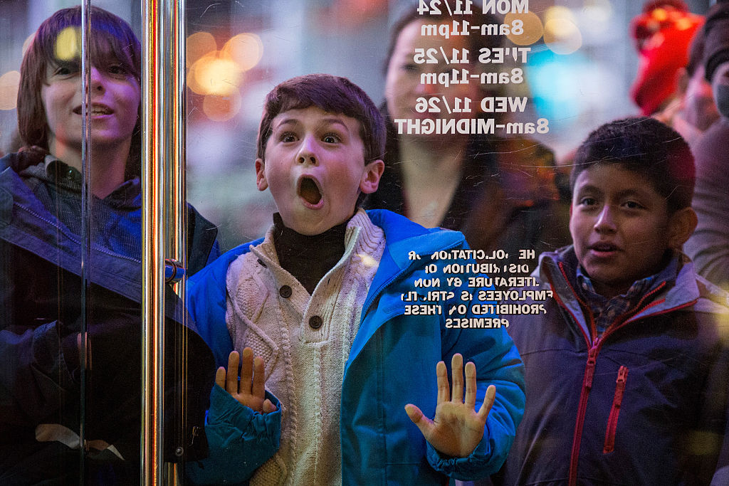 a kid presses his face against the glass at Toys R Us